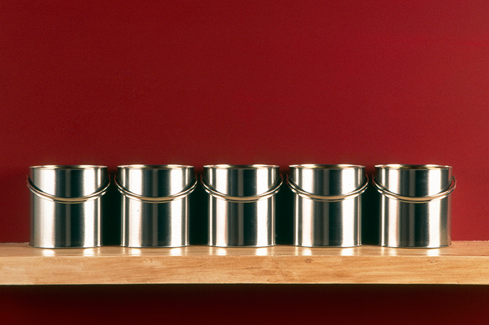 Room set image with red wall colour and silver paint cans lined up