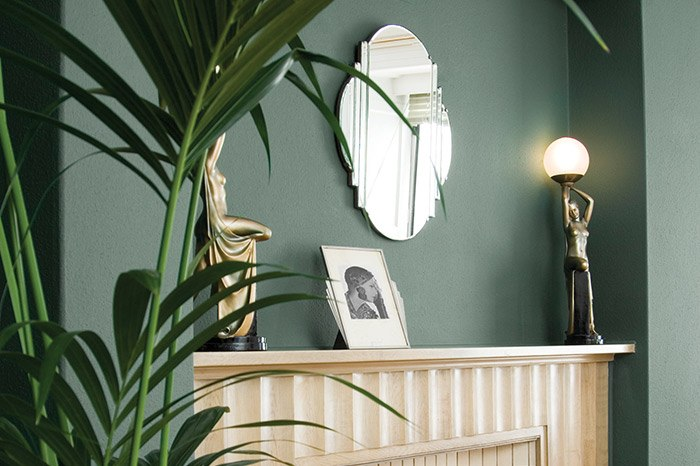 Room set image with green walls painted with Craig & Rose Angelica chalky emulsion finish